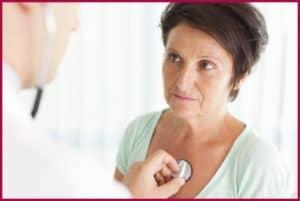 Женщину слушает врач