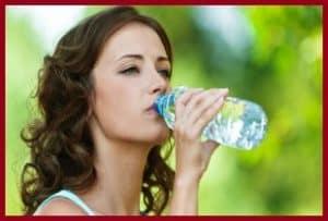 Женщина пьет из бутылки